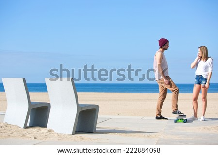 Encounter between a boy and a girl on a beach; both seem positively interested in each other - stock photo