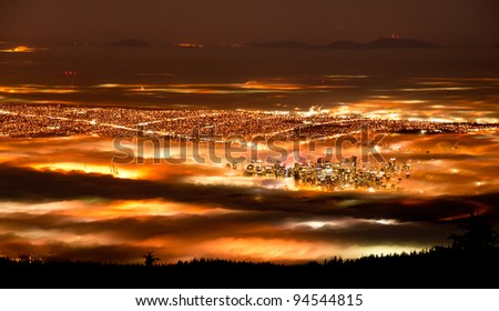 Encroaching fog shrouds the city of Vancouver, BC Canada at night - stock photo