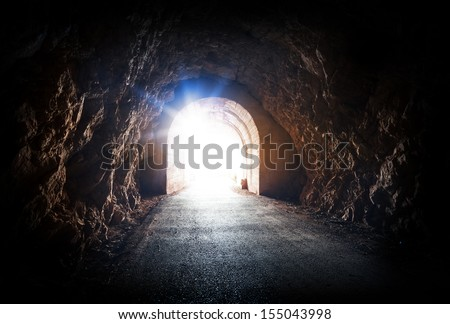 End of dark tunnel with magic blue light from the outside - stock photo