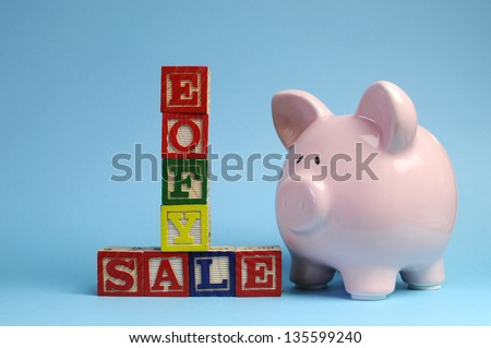 End of Financial Year sale message on building blocks with piggy bank on pale blue background.