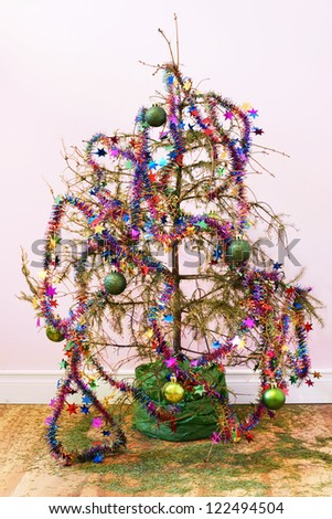 End of the holidays or other concept: dead fir Christmas tree with dried up needles all over the wood floor; star garland and ornaments left in the tree. - stock photo