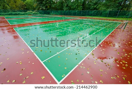 End of the season at tennis court covered with the leafs at autumn, fall time. Rainy day. - stock photo