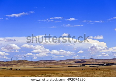 endless agricultural fields in South Australia with a chain of distant wind turbines on a hill top generating renewable power as part of industry and country development.