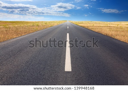 Endless driving on the asphalt road at sunny day. - stock photo