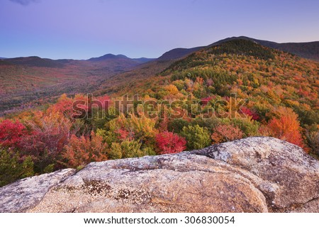 Endless forests with fall foliage in the White Mountain National Forest, New Hampshire, USA. Photographed from North Sugarloaf at dusk. - stock photo