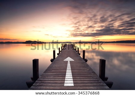 endless jetty with an arrow leading over lake to the horizon. Concept for proceeding to success.