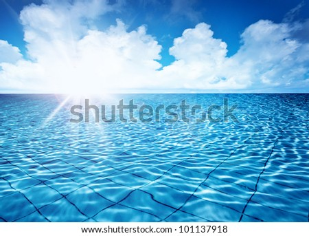 Endless pool water with blue sky background and bright sun light, fresh natural landscape, rippled texture and pattern, swimming pool seamless surface, summer travel vacation and spa leisure concept - stock photo