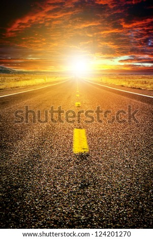 Endless road in the sunset light - stock photo