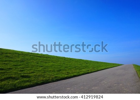 Endless road to nowhere with blue sky and green meadow