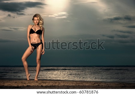 Endless sky. Young woman posing on beach in bikini at sunset with sea in background. - stock photo