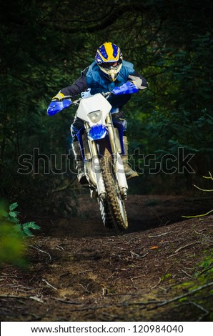 Enduro bike rider on action. Small jamp on muddy terrain. - stock photo
