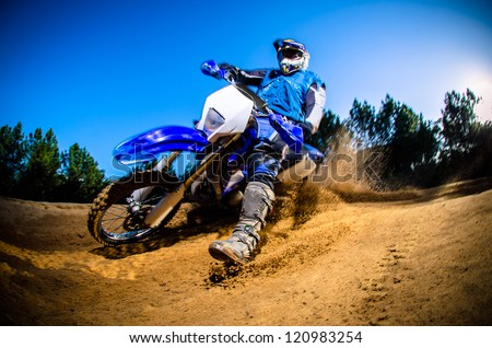 Enduro bike rider on action. Turn on sand terrain. - stock photo