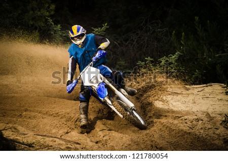 Enduro bike rider on action. Turn on sand terrain. - stock photo
