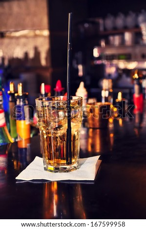 energetic alcoholic beverage on bar with straw and whiskey with  nightclub background - stock photo