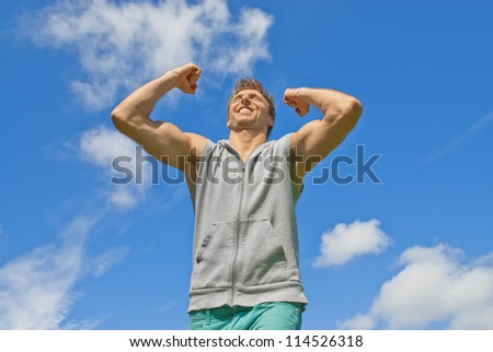 Energetic and happy young man on blue sky background. - stock photo
