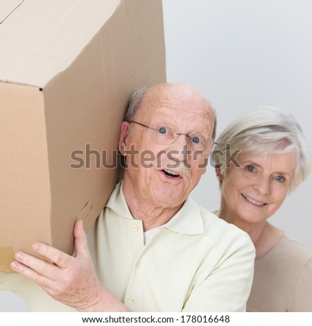 Energetic attractive senior couple moving home carrying out a cardboard box together and laughing at the camera, closeup of their faces - stock photo