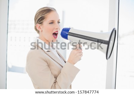 Energetic blonde businesswoman in bright office shouting in megaphone