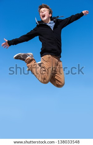 Energetic boy jumping and shouting outdoors.
