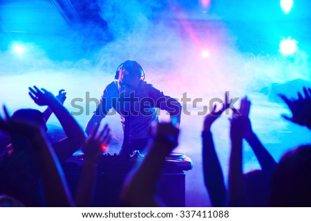 Energetic deejay standing in front of dancing people in club - stock photo