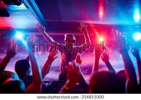 Energetic deejay with headphones having fun by turntables in front of dancing crowd - stock photo