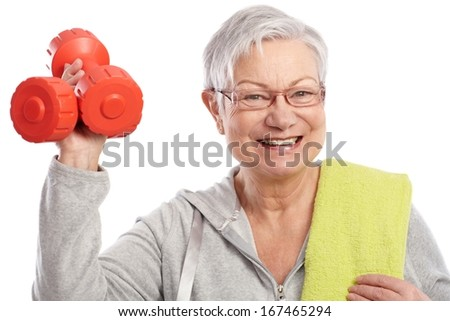 Energetic elderly woman holding dumbbells, smiling. - stock photo