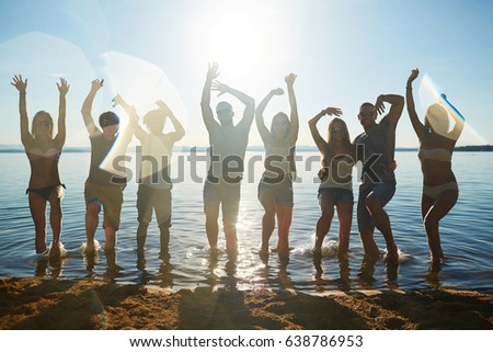 Energetic friends dancing in water by sandy beach