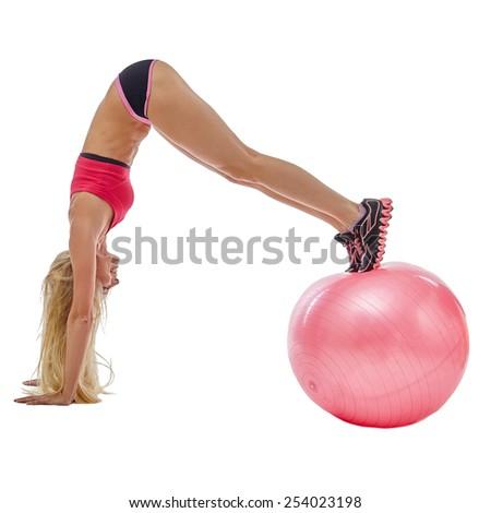 Energetic girl doing handstand on fitness ball - stock photo