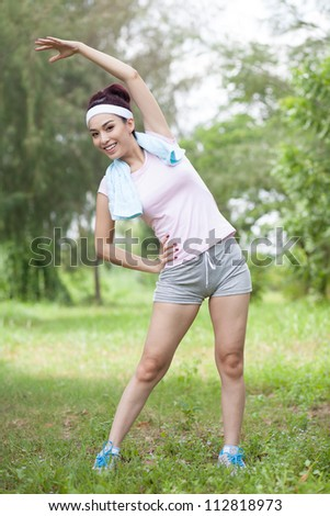 Energetic sportswoman performing lateral stretch