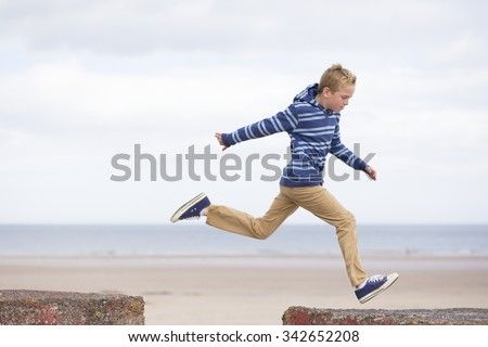 Energetic teenage boy jumping from one rock to another with the beach in the background.  - stock photo