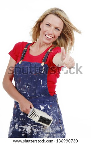 Energetic woman with paint brush thumbs up - stock photo