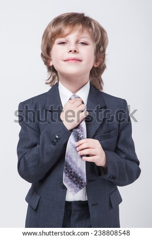energetic young successful businessman in a classic suit straightens his tie and smiling - stock photo