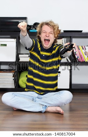 Energized teenage boy playing game, pumps his fist.Winner - stock photo