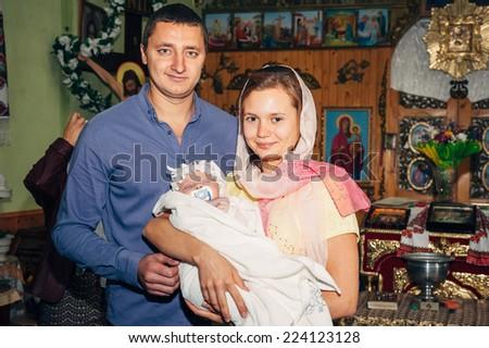 Energodar, UKRAINE - September 24, 2014: The Holy Orthodox rite of the sacrament of baptism newborn baby in a small wooden Christian Church September 24, 2014 in Energodar, Ukraine. - stock photo