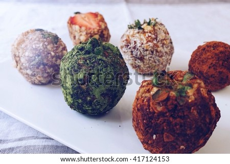 Energy ball  ; made with grilled almond, cashew nut, sunflower seed, fig, grill coconut crated, granola and fresh strawberry stuffed finishing with cocoa powder,  matcha green and coconut crated.