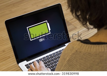 energy concept: full battery on a laptop screen. Screen graphics are made up. - stock photo