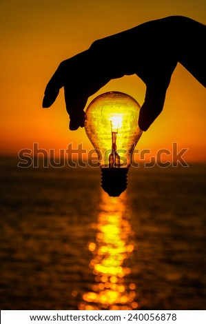 Energy Concept Light Bulb and Sun Setting on the Atlantic Ocean - stock photo