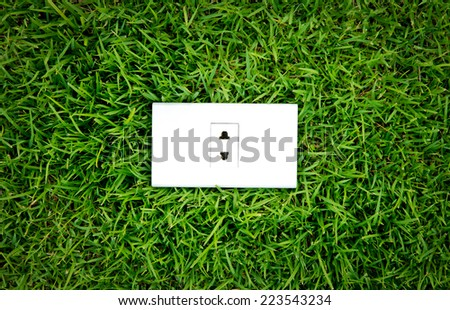 Energy concept outlet in fresh spring green grass - stock photo