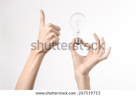 Energy consumption and energy saving topic: human hand holding a light bulb on a white background in studio