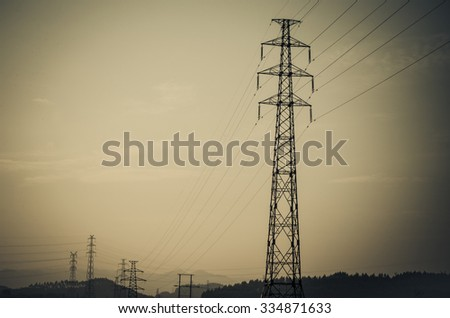 Energy Distribution Network - Electricity Pylons against Orange and Yellow Sunrise