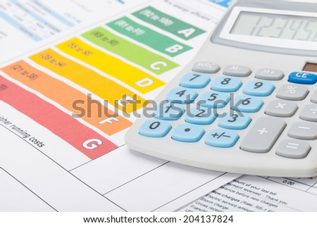Energy efficiency chart with calculator - studio shot - stock photo