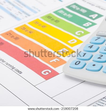 Energy efficiency chart with calculator - studio shot - 1 to 1 ratio - stock photo