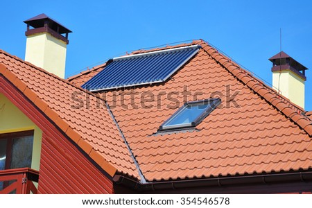 Energy efficiency concept. Closeup of solar water panel heating on red tiled house roof with lightning protection, skylights, chimney and roof window - stock photo