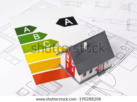 Energy efficiency label with model and architecture blueprint. - stock photo