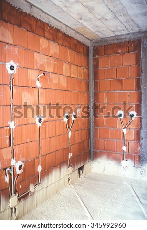 energy efficient house, built with top quality materials, thermal insulation and brick walls with plugs and electricity pipes - stock photo