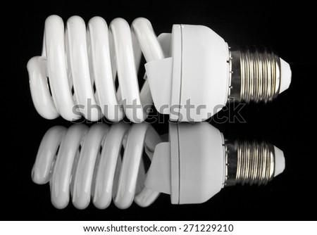 energy efficient light bulb on black background - stock photo