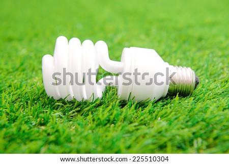 Energy efficient light bulb on green grass - stock photo