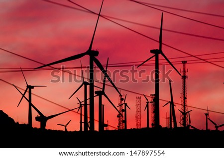 Energy generating wind turbines in Palm Springs at sunset. - stock photo