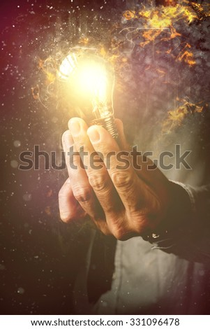Energy of new ideas in business process, businessman with light bulb as metaphor of new ideas, innovation and creativity, retro toned image, selective focus. - stock photo