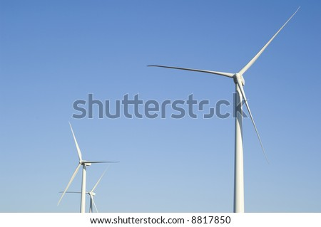 Energy producing wind turbines against a blue sky with copy space
