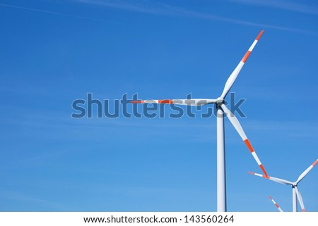 Energy producing windmills against blue sky - stock photo